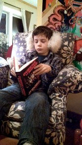 Kjel, nephew of Allison Wolfe, reads Queens of Noise. courtesy http://www.lastgasp.com/story/2014/05/kidsread3